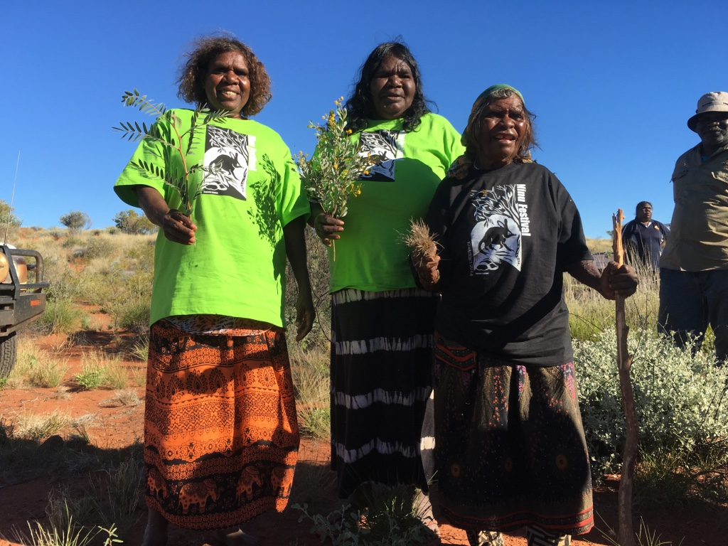 Kiwirrkurra_rangers_Sally_Butler__Monica_Jurrah__Josephine_Nungala_show_festival_attendees_plants_associated_with_bilby_food_on_country.jpeg