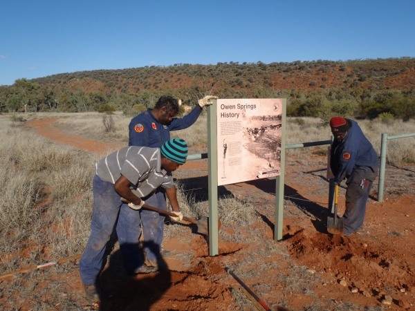 Tjuwanpa Rangers erecting park signage at Owen Springs Reserve as part of Joint Management work
