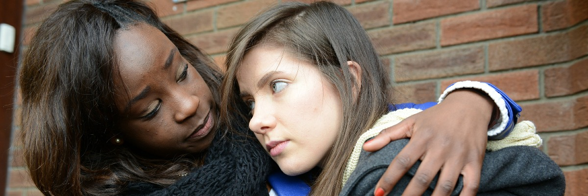 Woman comforting girl.