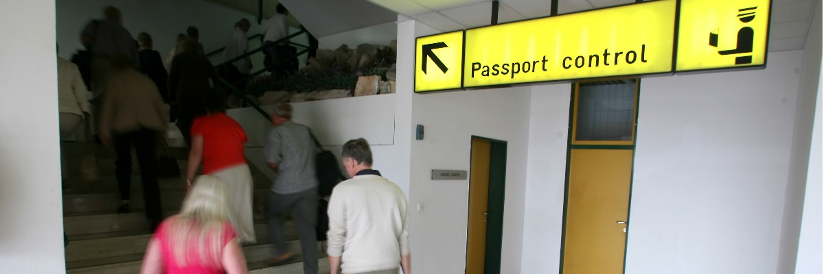 A sign pointing to passport control, with people climbing a flight of stairs in the background.
