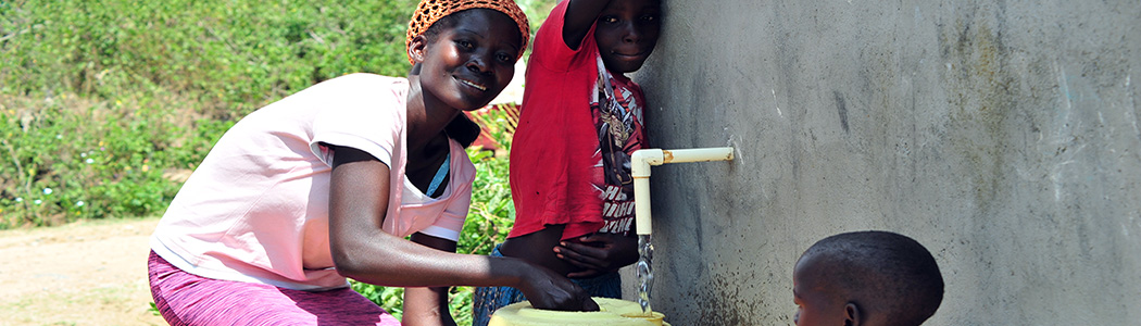 Photograph of a woman collecting water
