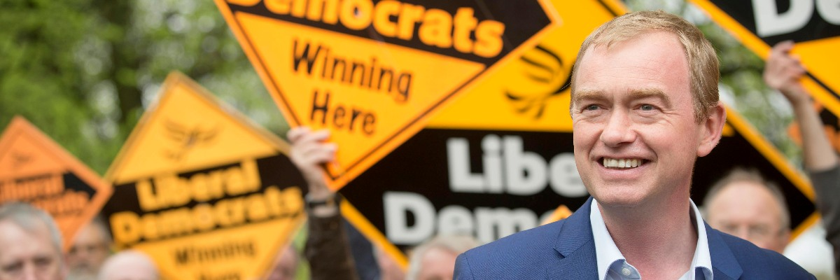 Tim Farron in front of activists holding Lib Dem diamonds.