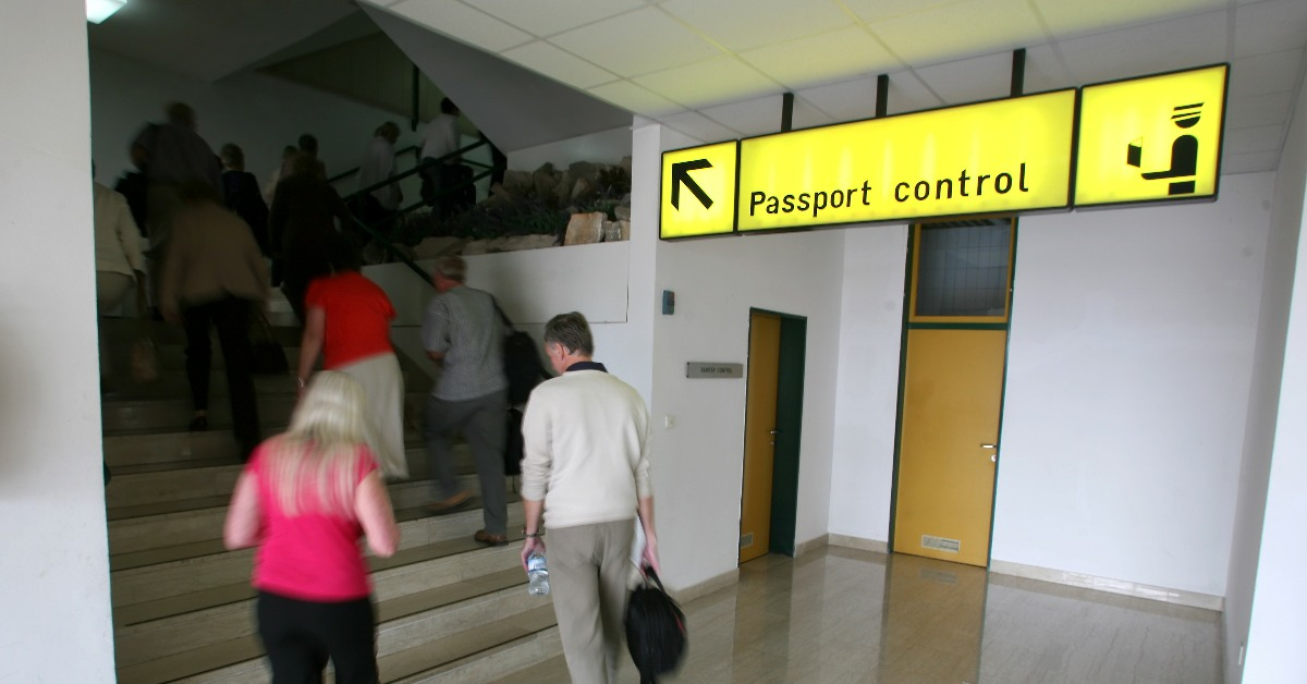 A sign pointing to passport control, with people climbing a flight of stairs in the background. Links to: Deprivation of Citizenship