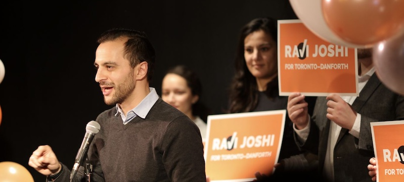 Ravi Joshi on a stage in front of supporters. They are holding signs that say Ravi Joshi for Toronto-Danforth.