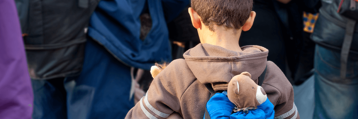 A child refugee with teddy bear in backpack
