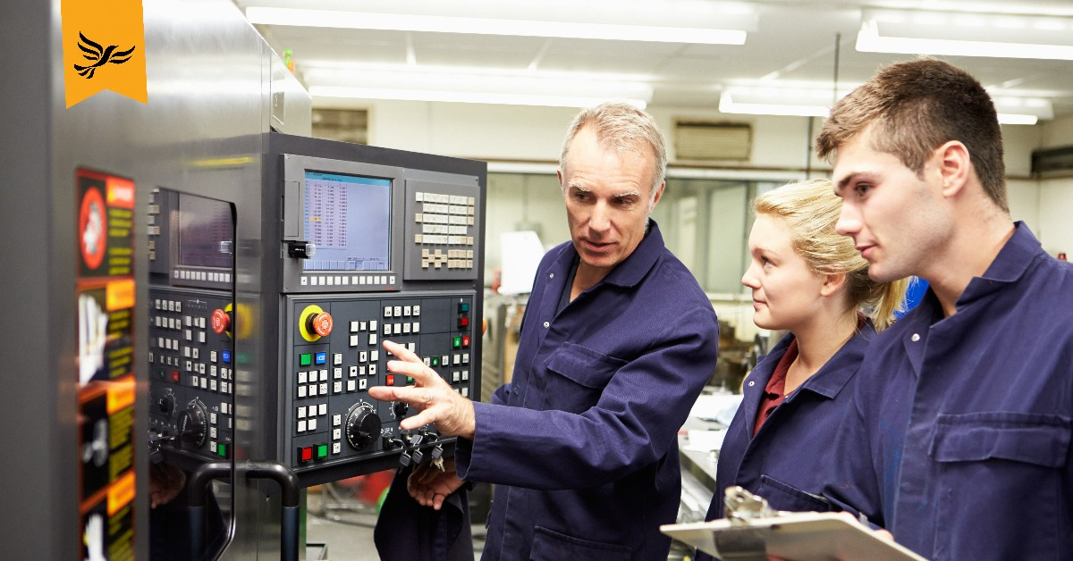 Two apprentices looking at a machine, at which their instructor is pointing.