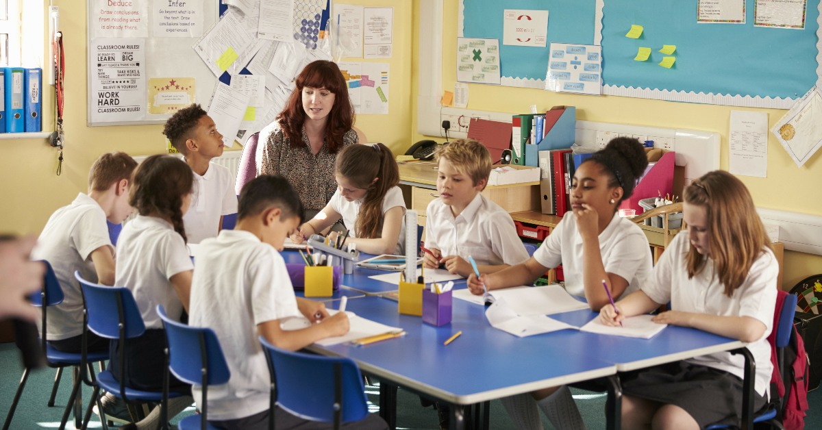 Eight schoolchildren working at a table supervised by a teacher.