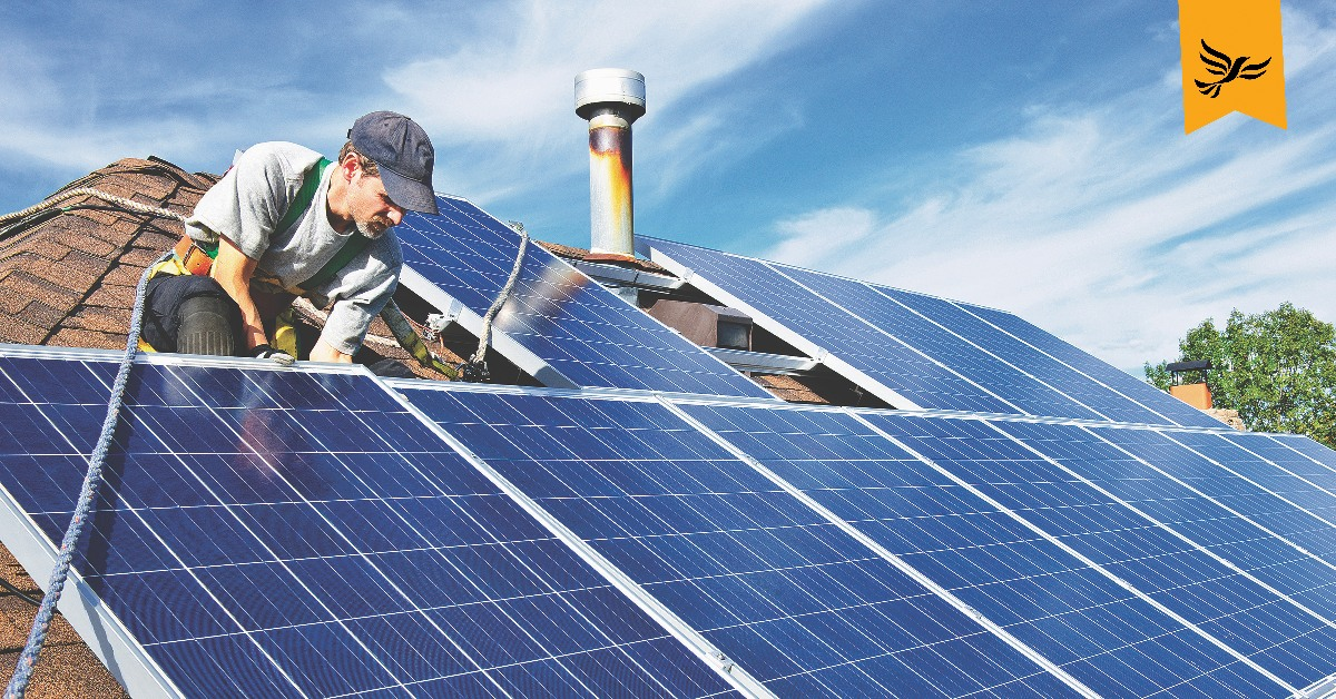 A worker fitting solar panels on a roof.