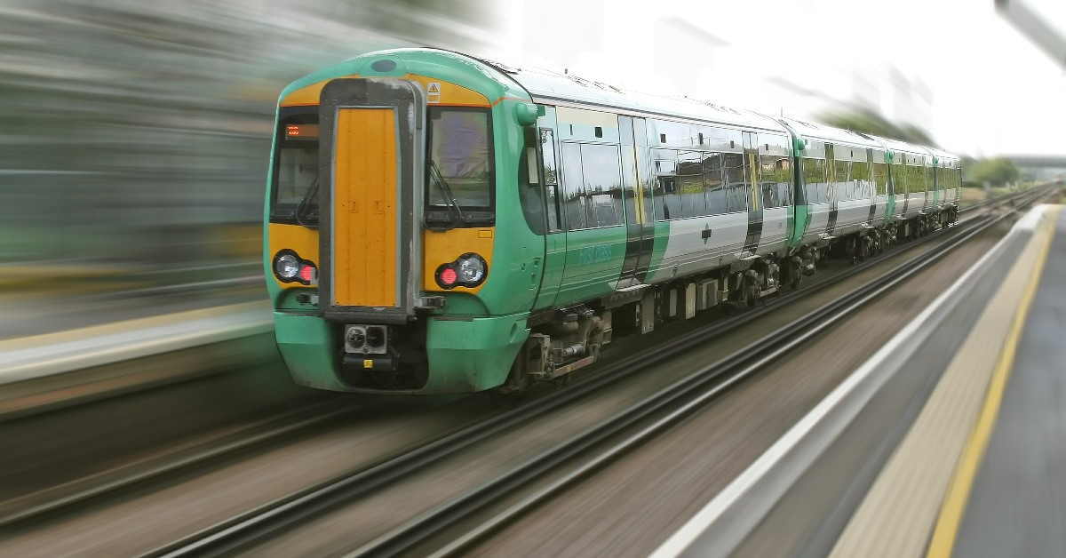 A Southern Rail train passing through a station at speed.