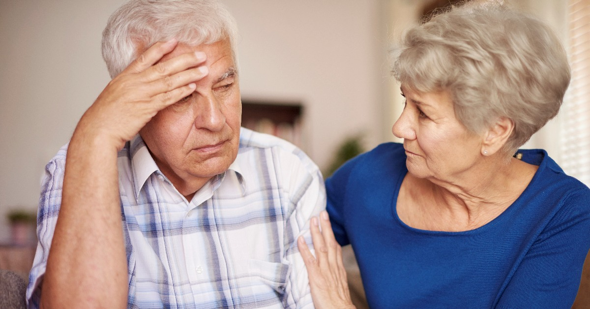 An older man with his hand on his head, being conforted by an older woman.