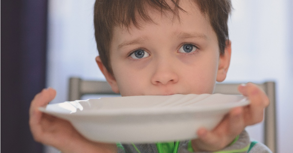 Hungry child holding bowl.