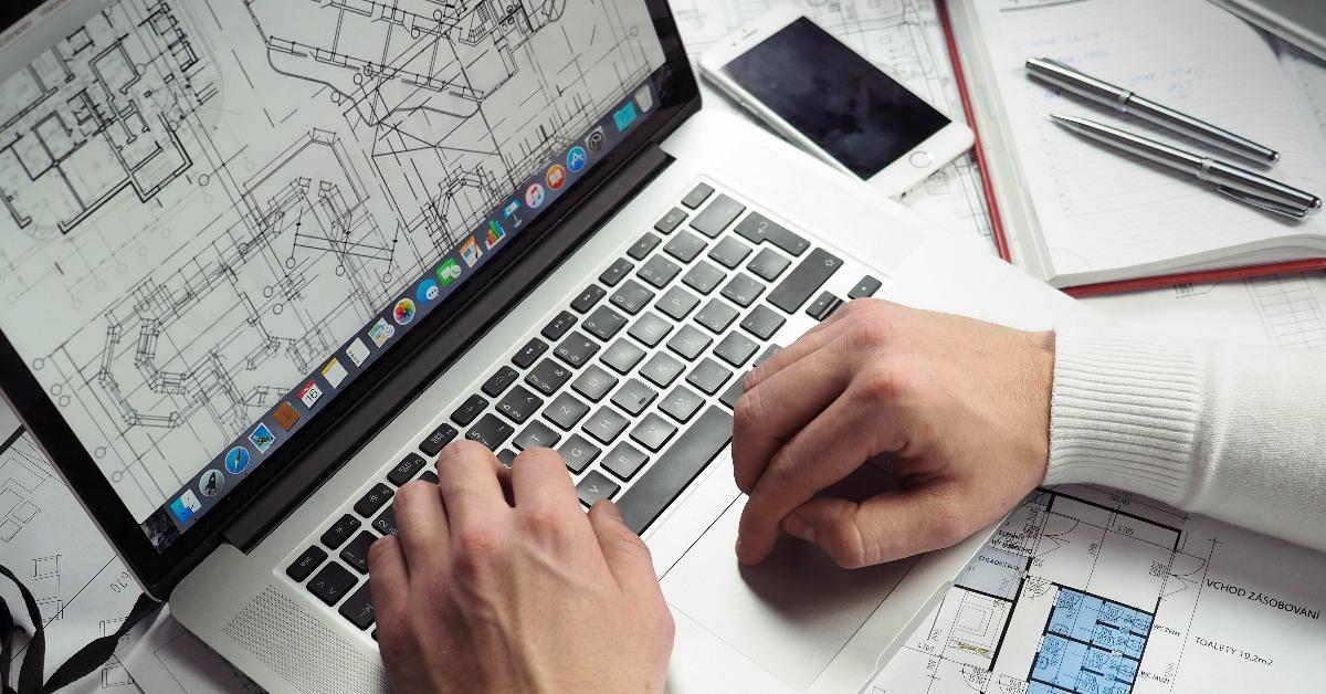 Plans on Macbook screen, hands operating laptop.
