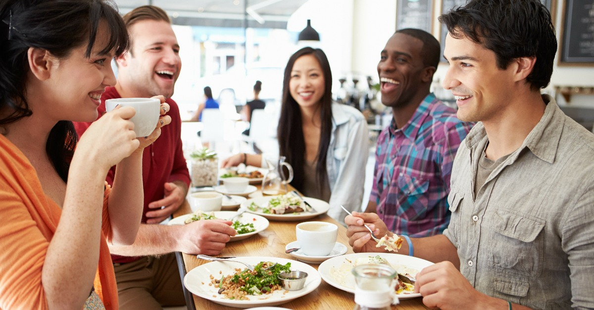Five young people chatting over coffee and eating salads, possibly including avocado.