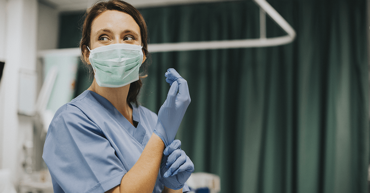 Medic in scrubs and mask pulling on a glove