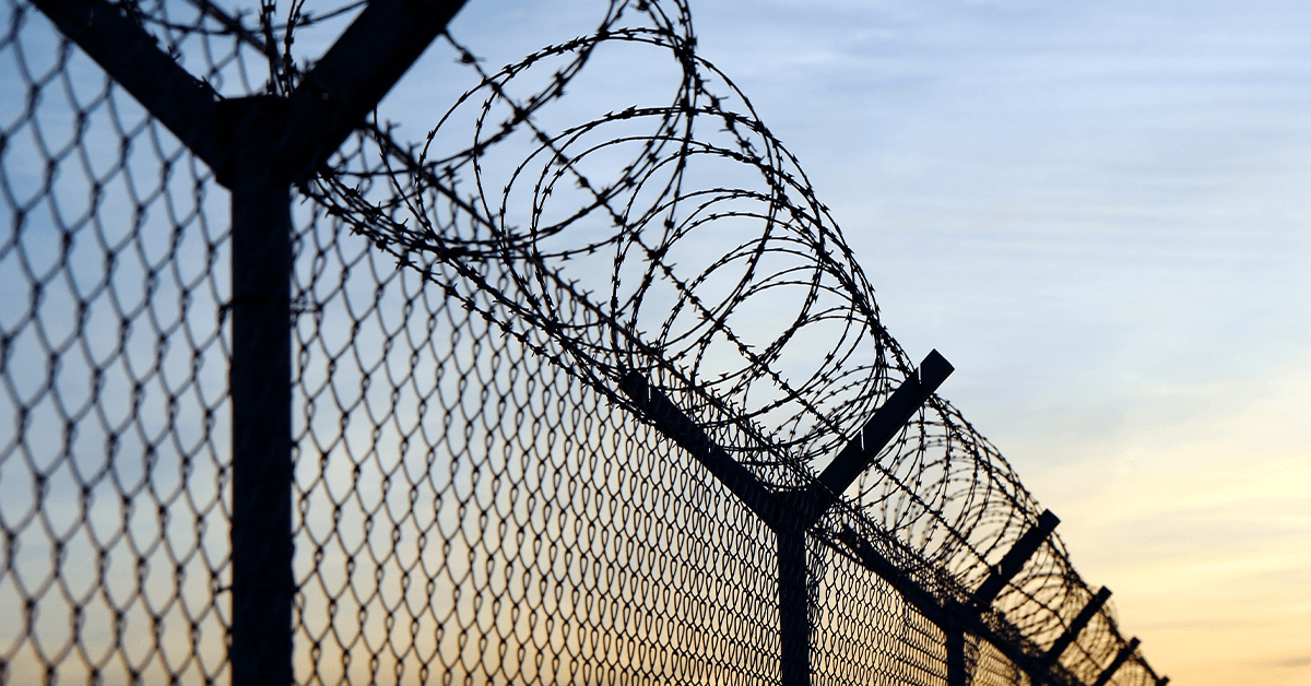 A metal fence topped with barbed wire