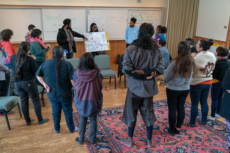 People standing in a circle looking at a whiteboard as a man talks at the Bay Area Land Justice Convening 2019. Photo credit: Mateo Hinojosa, The Cultural Conservancy