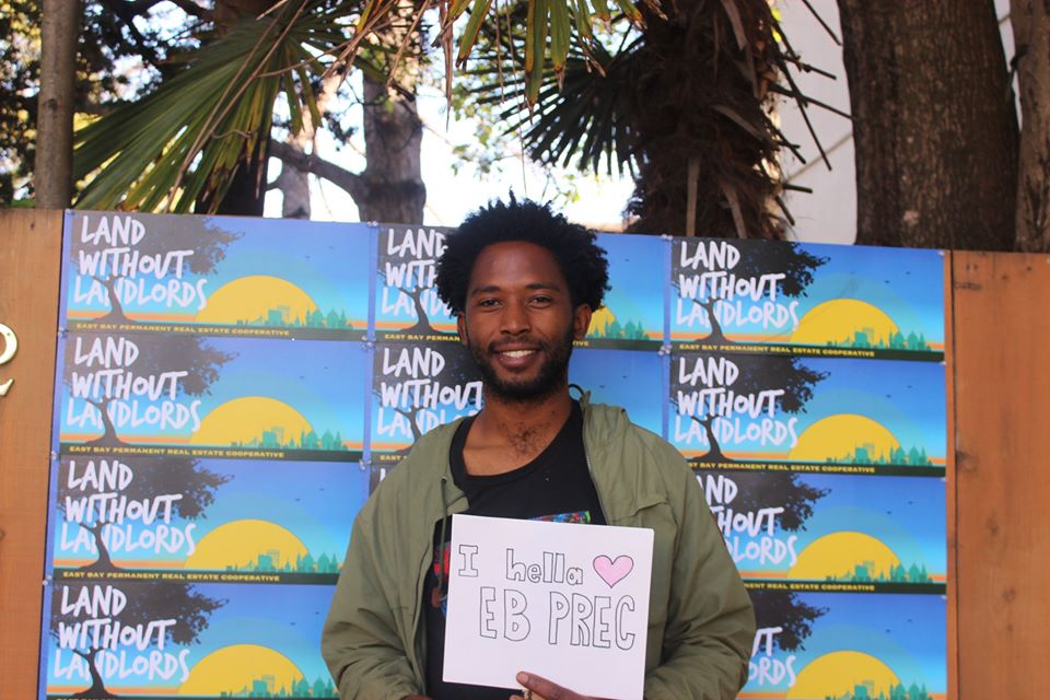 "Greg Jackson, EB PREC staff owner, stands in front of a sign reading ""Land without Landlords"" holding a sign that reads ""I hella <3 EB PREC"""