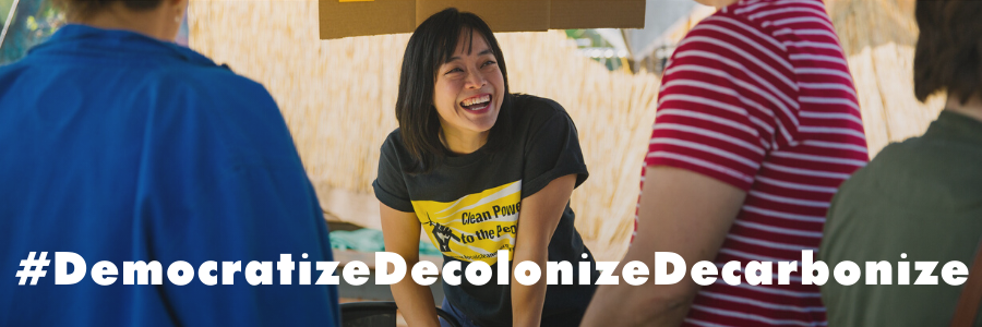 Image: People Power Solar tent, text: #DemocratizeDecolonizeDecarbonize