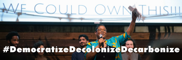 Image: Noni with her fist up, text: #DemocratizeDecolonizeDecarbonize