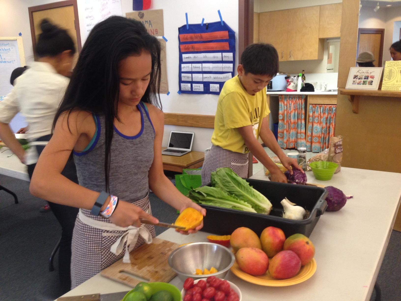 Older Sama Sama camp participants prep vegetables for lunch