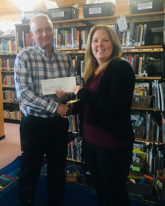 Hornepayne Public Library CEO Darnelle Hill accepting donation from Society of United Professionals' NWMO Local