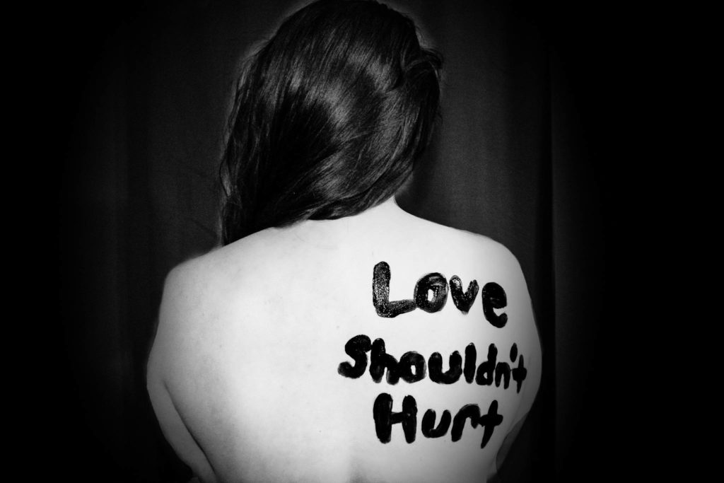 Woman with Love Shouldn't Hurt written on her back