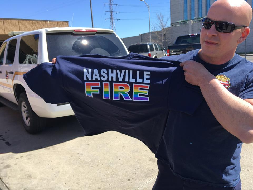 "Nashville Fire employee displaying navy NFD shirt with the word ""fire"" in rainbow letters"