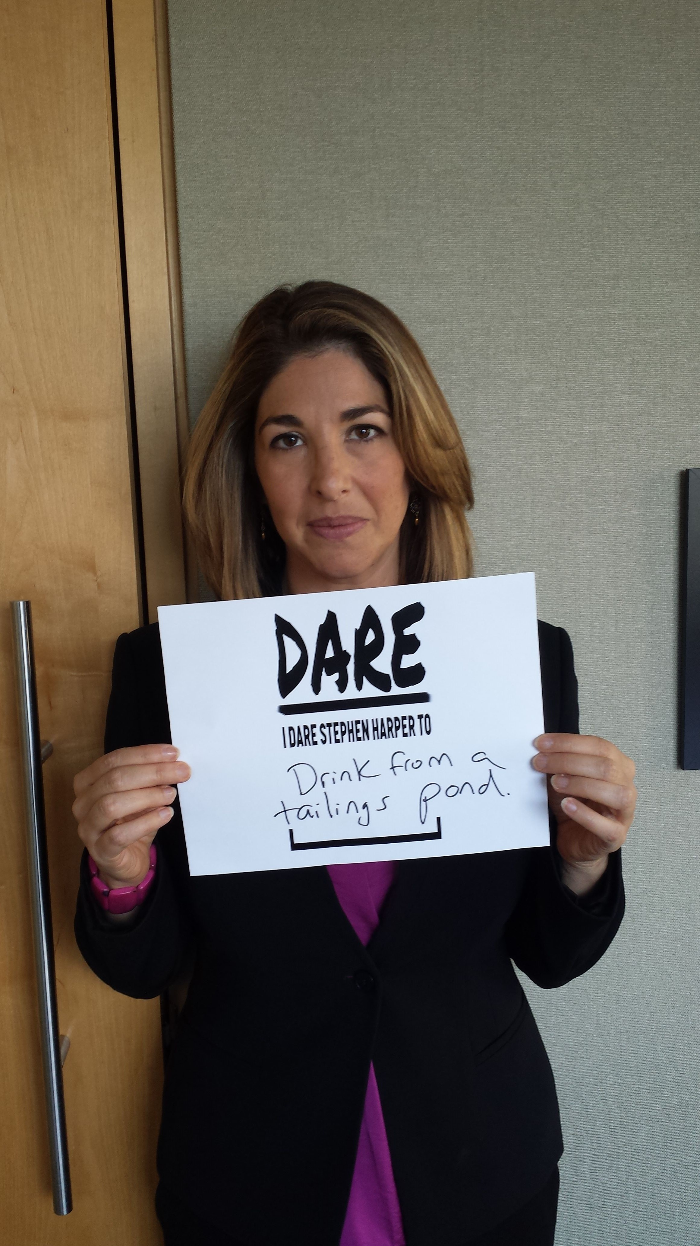 Naomi Klein holds a sign daring Stephen Harper to drink water from a tailings pond