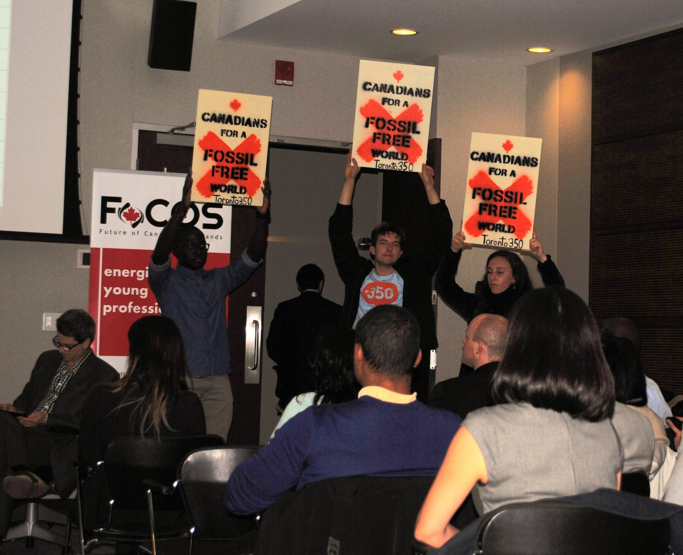 Members of Toronto350 hold up signs at so called sustainable tar sands discussion
