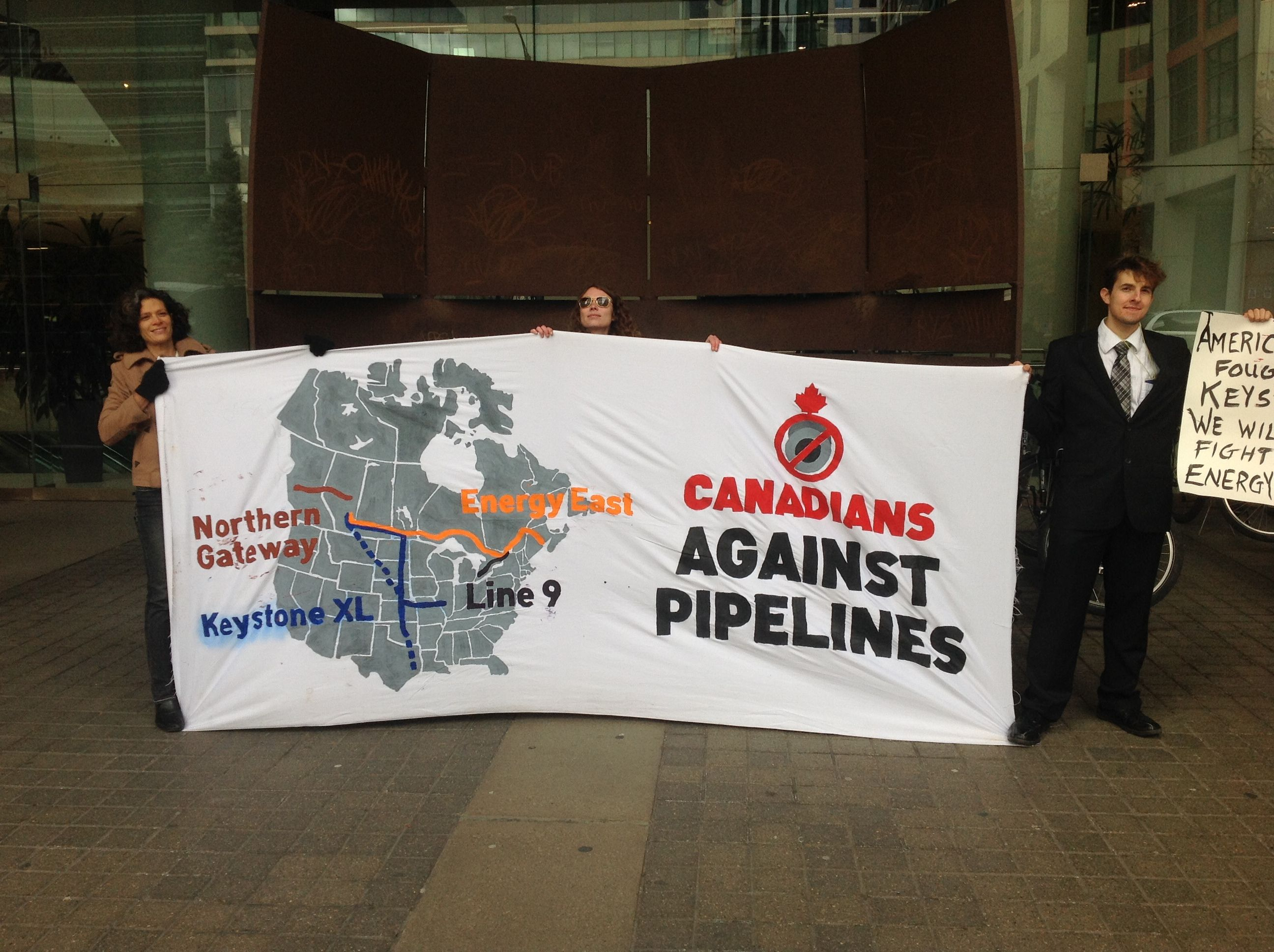 Protestors hold a banner that reads Canadians Against Pipelines