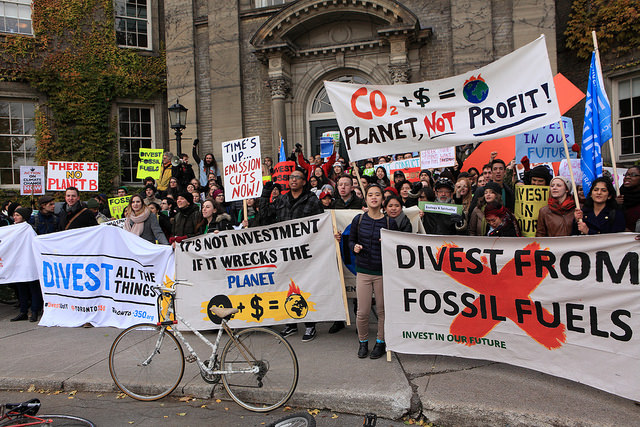 Students hold banners saying divest from fossil fuels