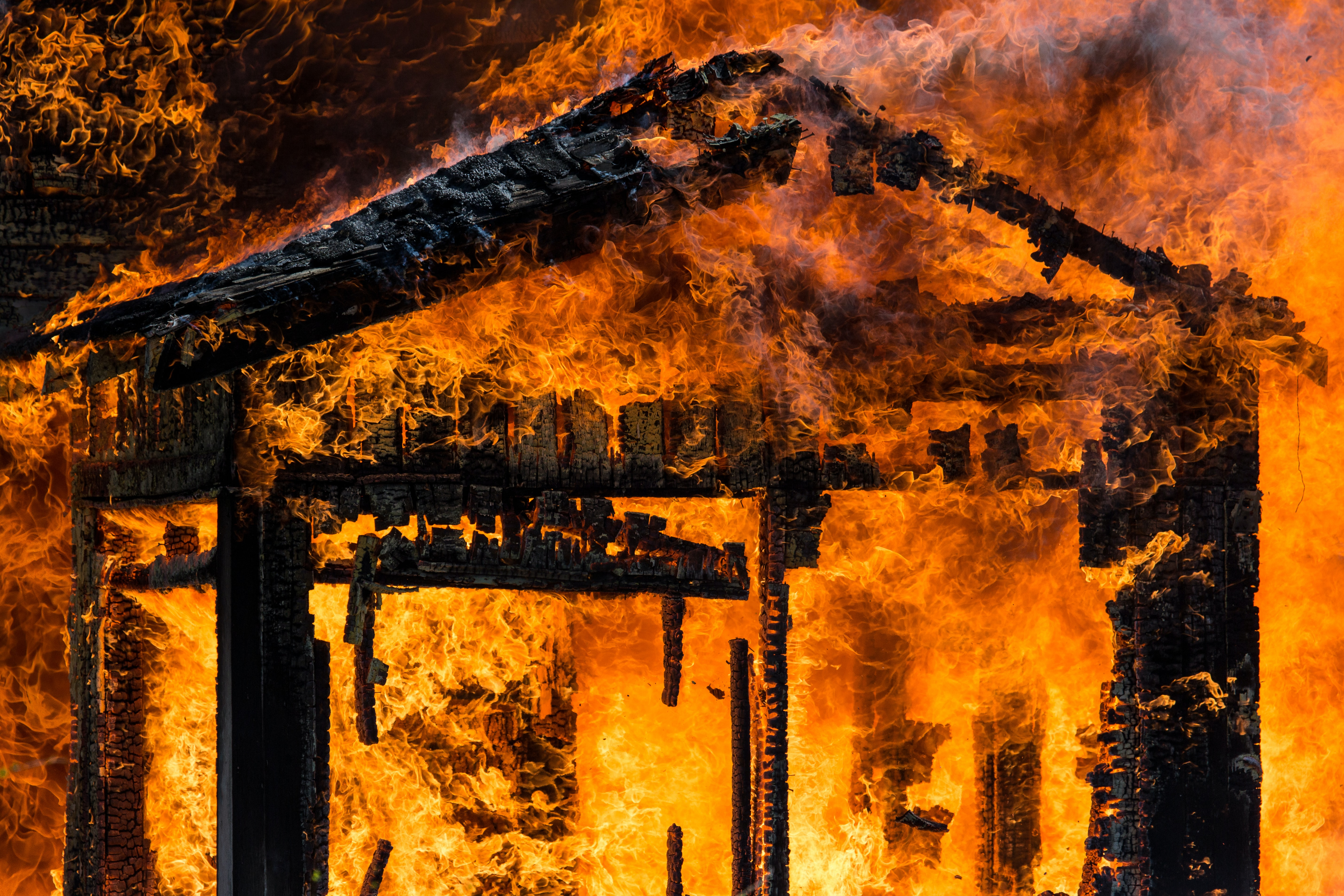 Photo of a house frame engulfed in flames, by Dave Hoefler
