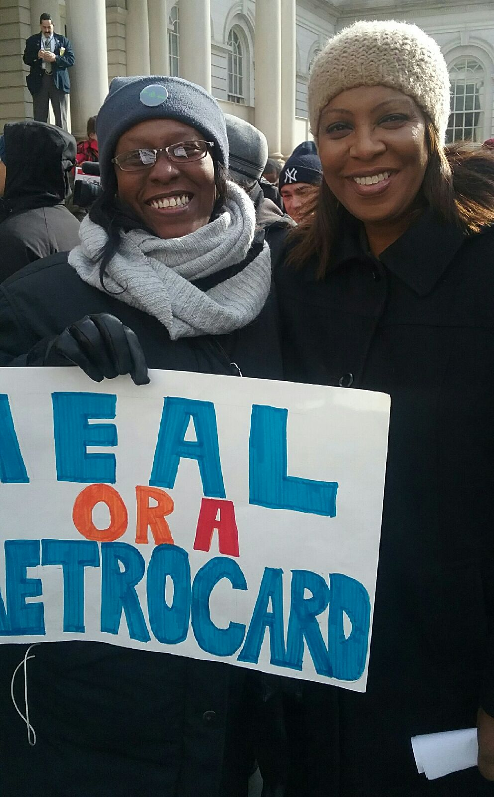 A member of TONYC stands with a public advocate at the rally
