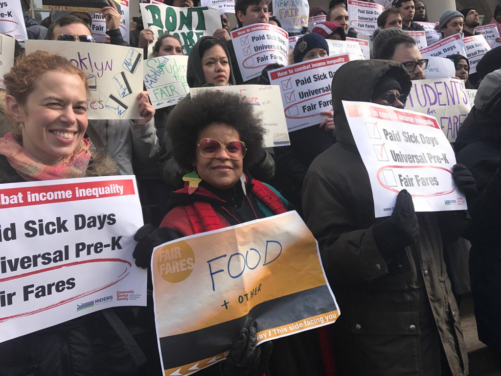 Members of TONYC stand in a crowd at the rally for fair fares