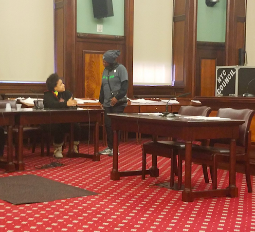 Two TONYC members act out a scene at the city council hearing