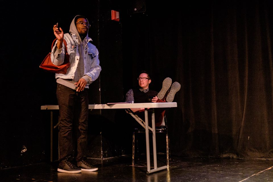 Two actors perform a scene onstage
