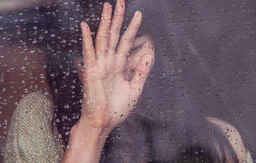 woman crying with hand on window