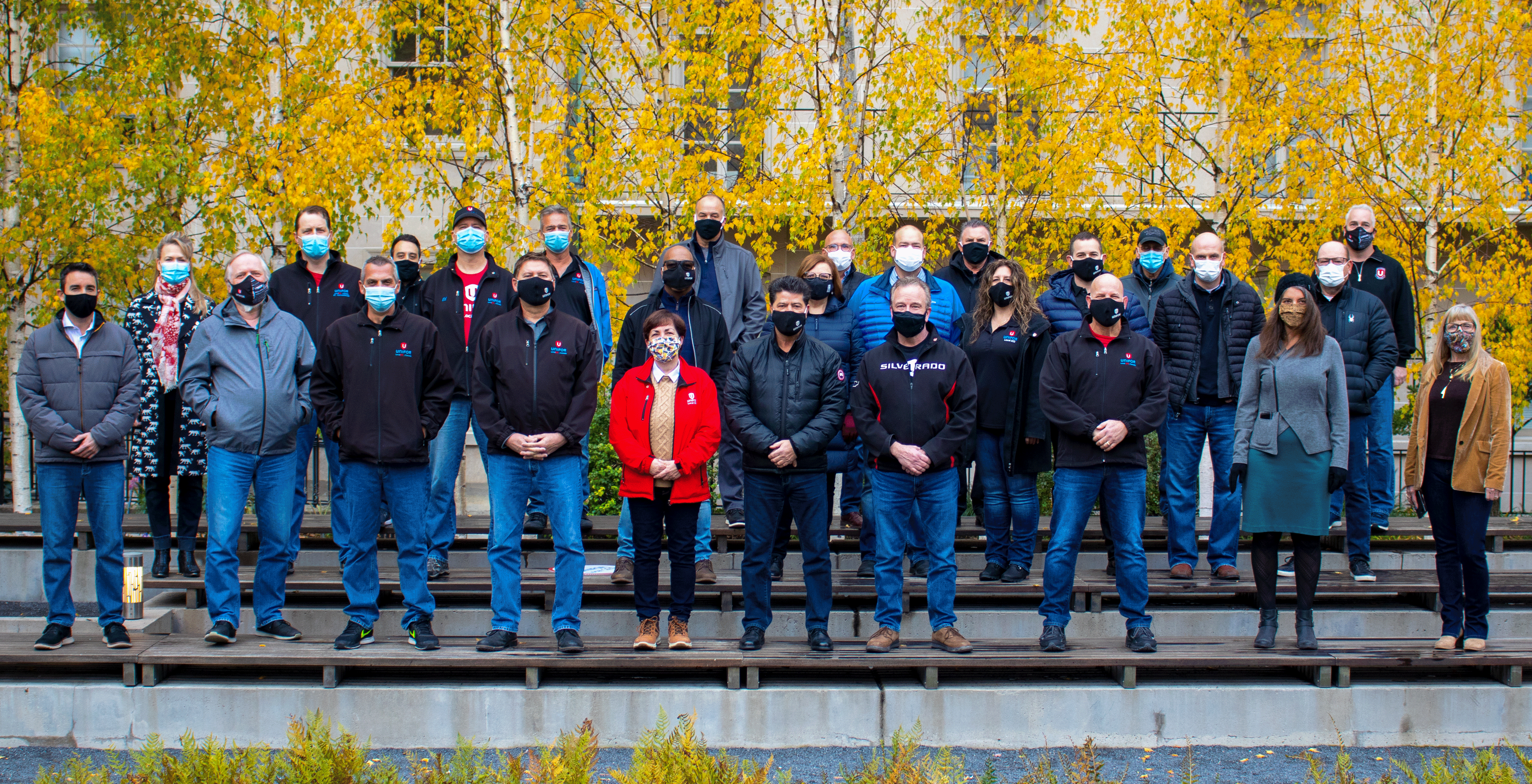 27 members of the GM bargaining committee pose on benched in front of trees.