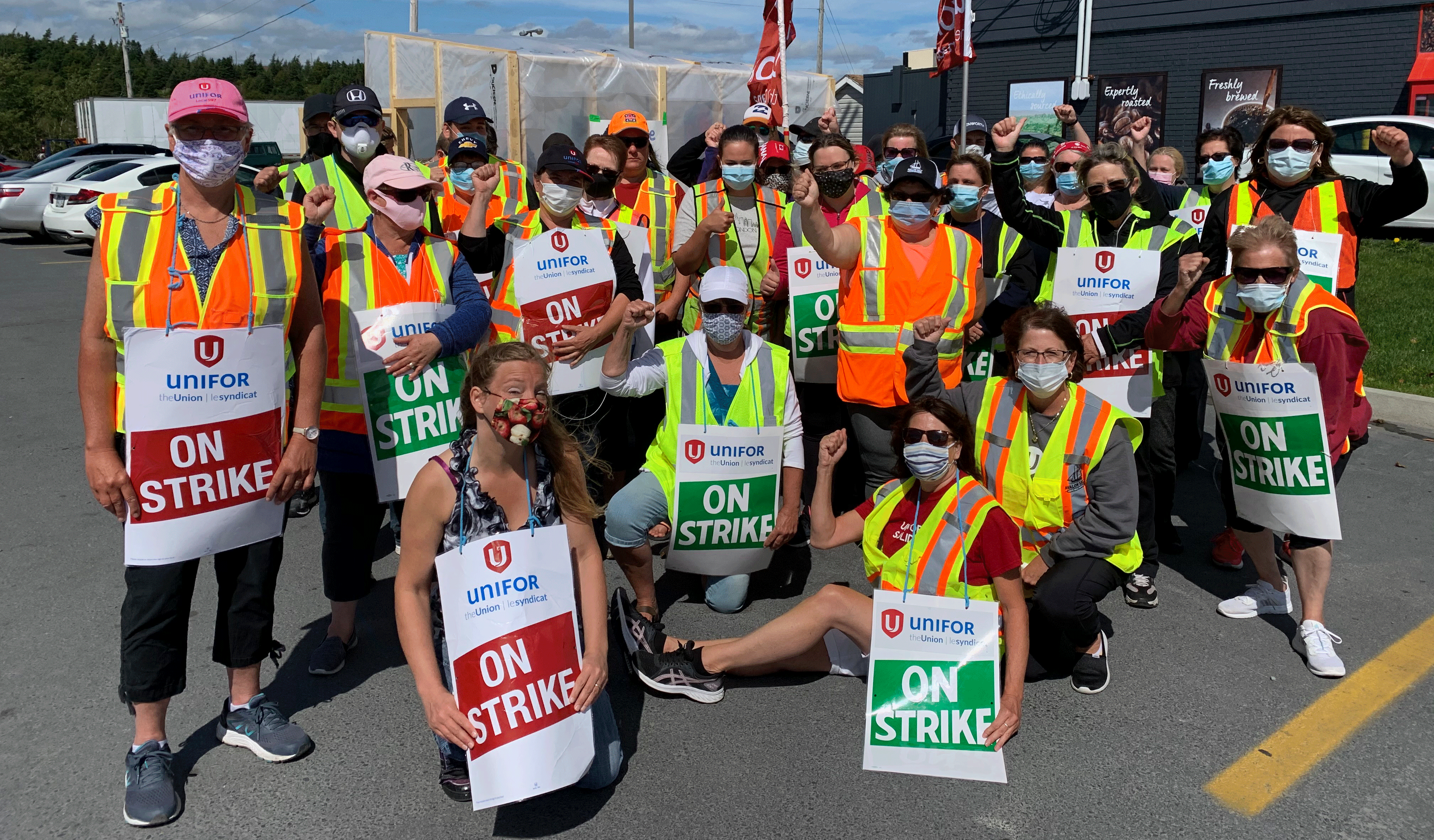 """Dozens of workers wearing masks and safety vests hold """"on strike"""" signs."""