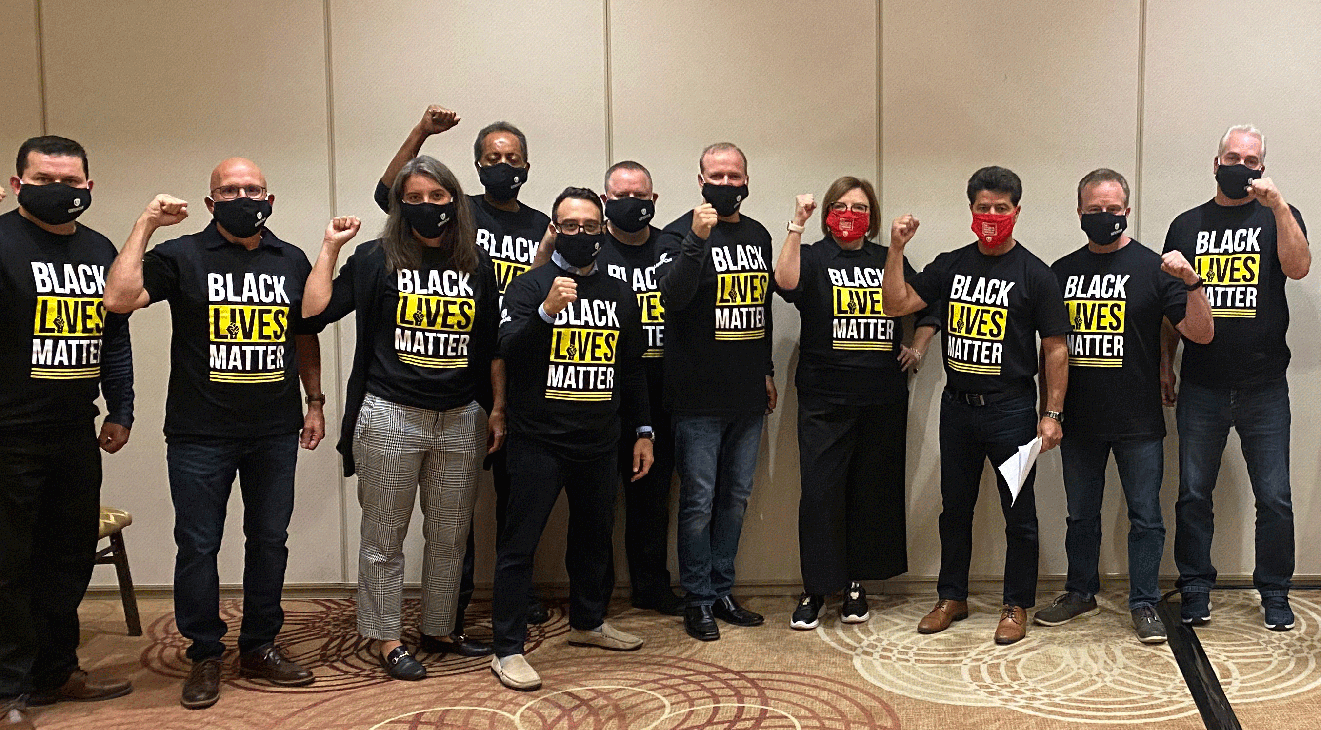 Unifor leaders and members wearing Black Lives Matter T-shirts raise fists.