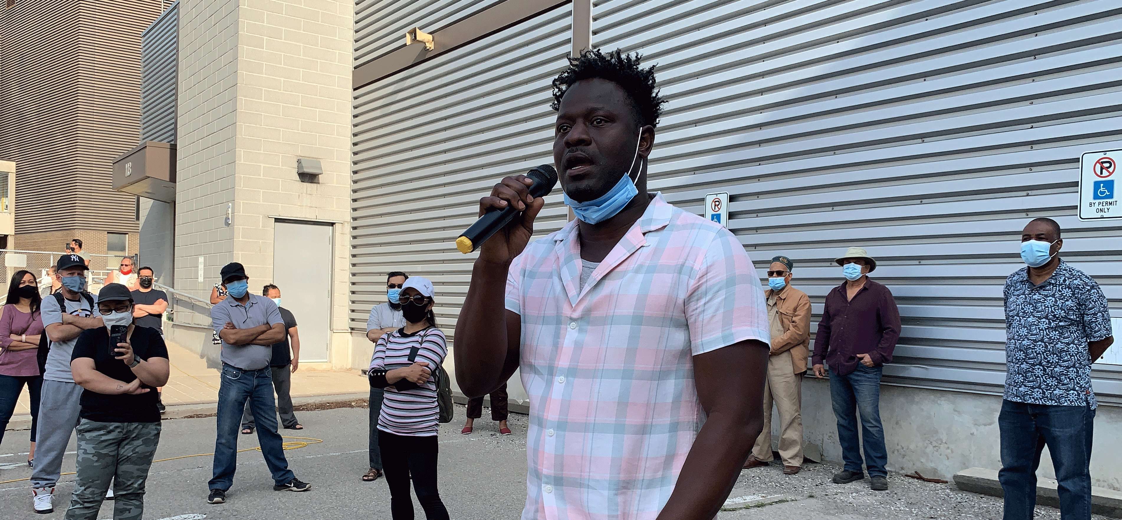 Un travailleur tient le micro alors que des dizaines de membres se rassemblent pour écouter sur la ligne de piquetage de Nestlé.