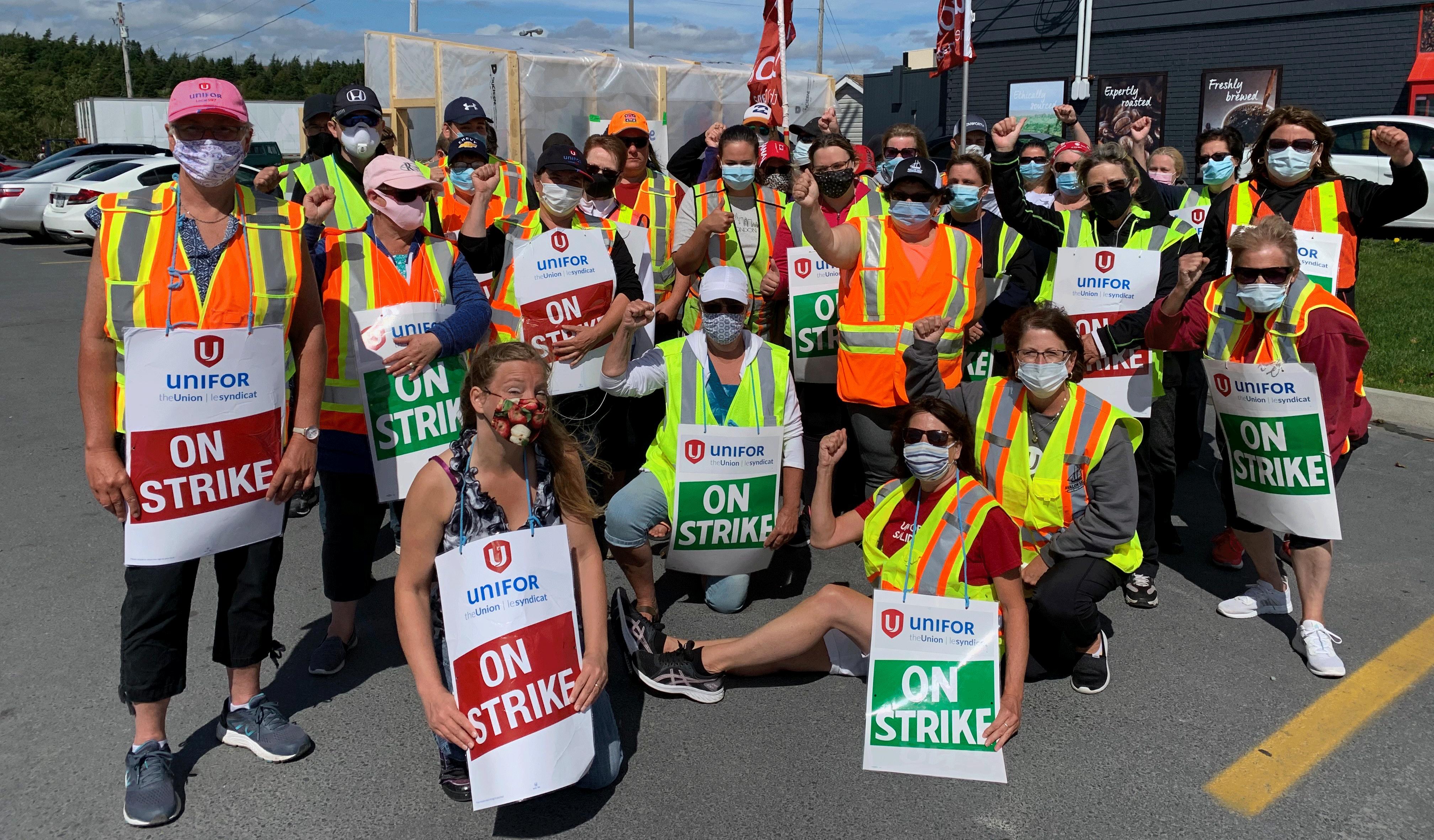Des dizaines de travailleurs portant des masques et des gilets de sécurité tiennent des pancartes « en grève ».