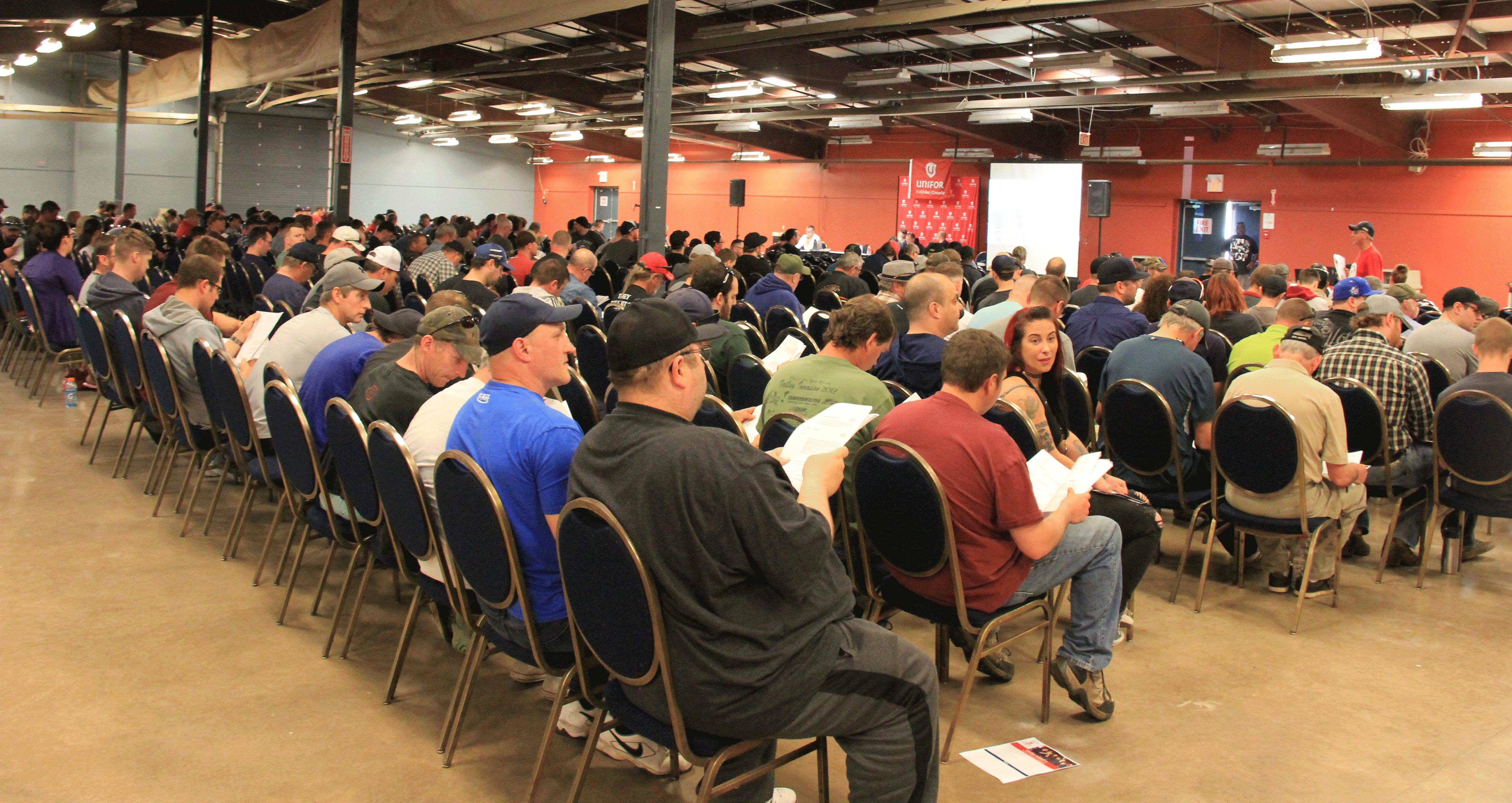 1 000 membres du chantier naval d'Halifax sont assis dans la salle de réunion lors d'une réunion de négociation.
