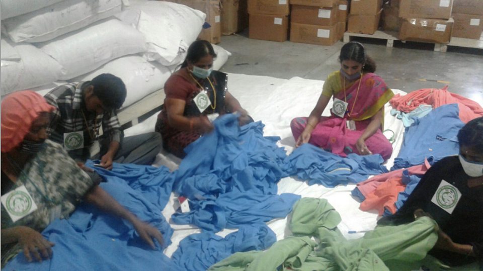 Women sewing clothing in their H&M factory in India wear stickers with the logo of the Cambodian call for a $177 minimum wage