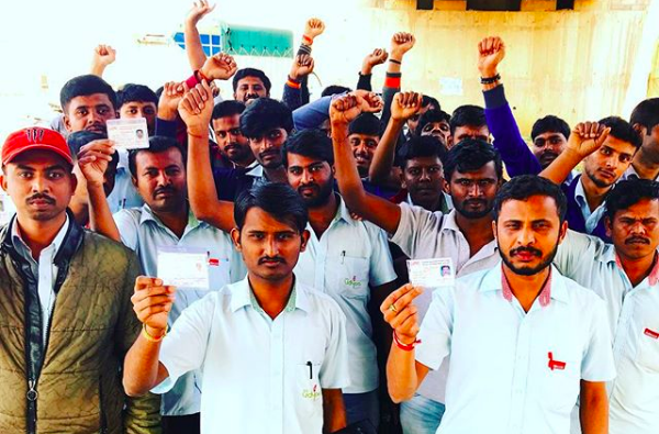 The contract workers of Avery Dennison Pvt. Ltd hold up their union cards, which they signed to stand up for their basic rights. They have been harassed and dismissed for standing up for their rights, but they are determined to stick with their colleagues and demand that Avery Dennison do the right thing!
