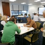 Open University tutor Chris Hill (standing) looks on as the groups works through one of the practical exercises.