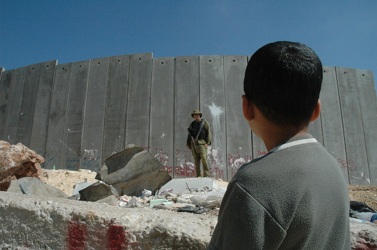 1200px-Boy_and_soldier_in_front_of_Israeli_wall.jpg