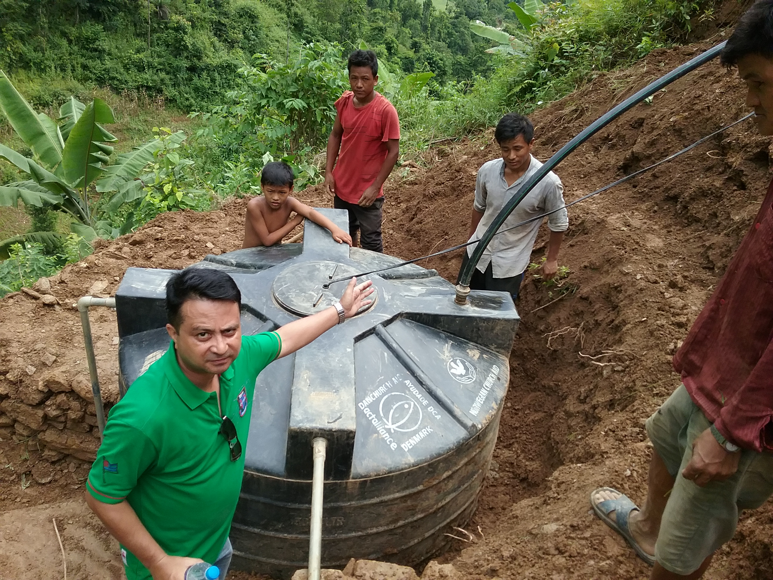 In Nepal's Dhading District, community members complete installation of their new water catchment tank, to collect water from the spring below their village.