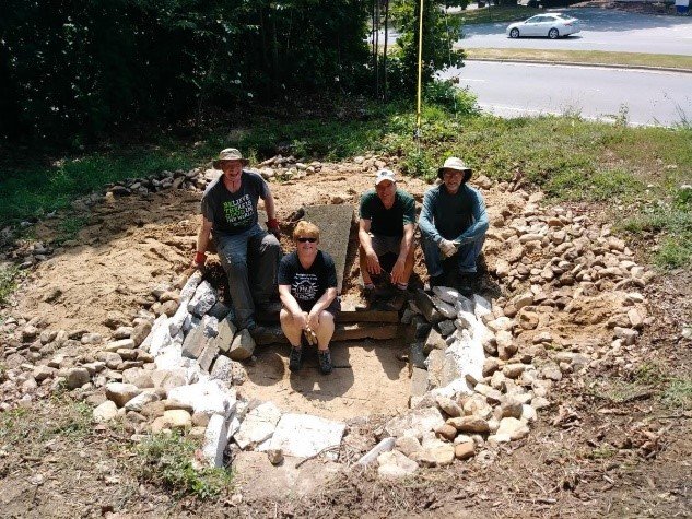 Volunteers create drainage bowl on church lot to capture water off parking lot used to water surrounding perennials