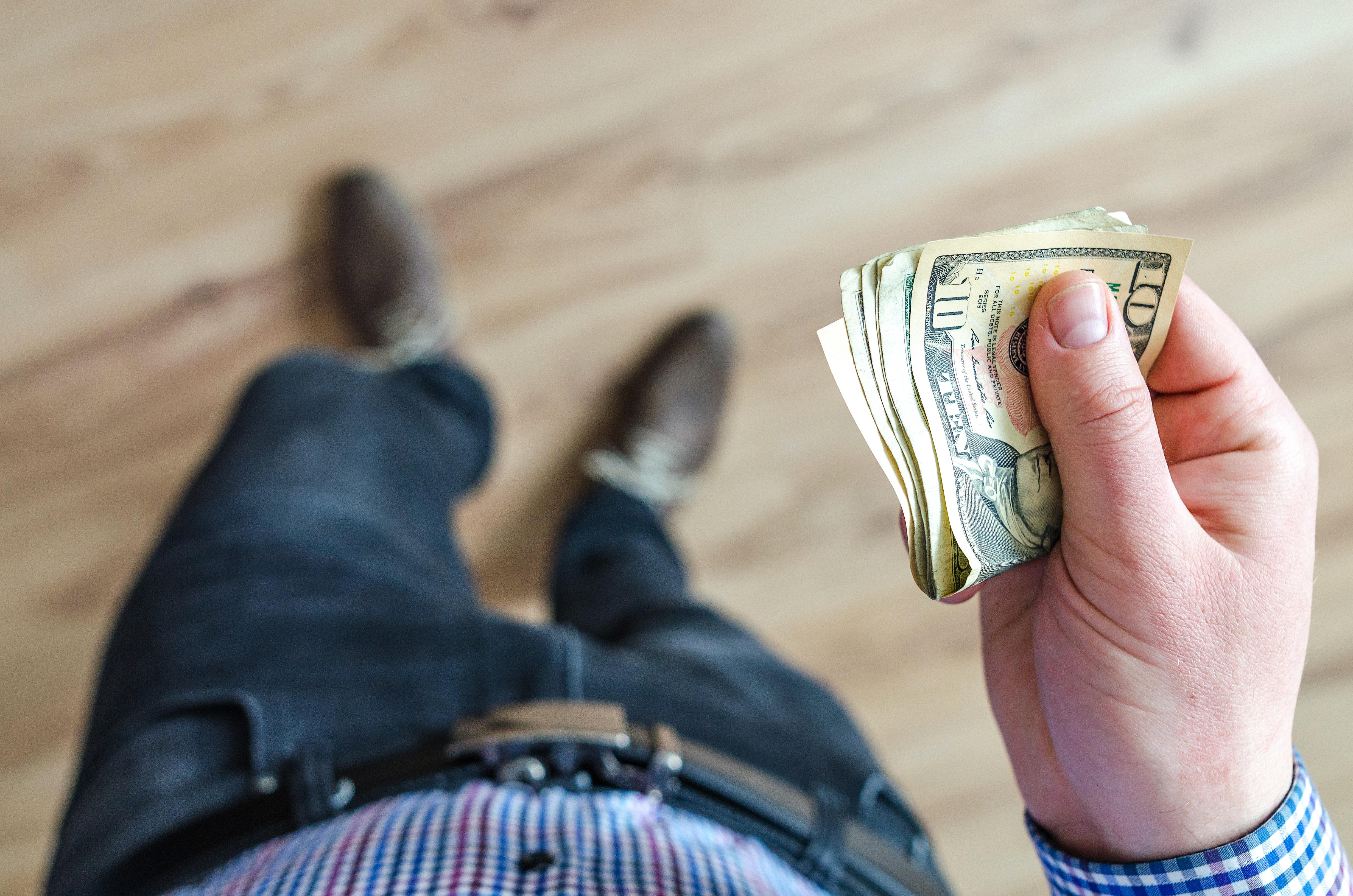 man-holds-10-u-s-dollar-banknote-928201.jpg